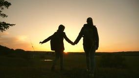 La madre y la hija del trabajo en equipo de vacaciones viajan con una mochila, aumentan sus manos para arriba admire el paisaje d metrajes