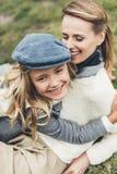 la madre y la hija elegantes felices en otoño equipan el abarcamiento Imagenes de archivo