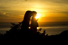 La madre y la hija en perfil hicieron excursionismo en la puesta del sol imagen de archivo