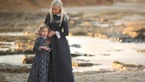 La madre y la hija están caminando a lo largo de la orilla