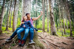 La madre y la hija est?n haciendo el selfie para sentarse en el tronco del ?rbol en un bosque fotografía de archivo