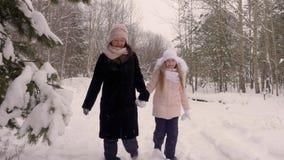 La madre y la hija felices de la mamá se unen a la mano y el paseo a través de las nevadas de maderas de árbol de pino de la tray almacen de metraje de vídeo