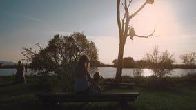 La madre y la hija hermosas jovenes se están sentando en un banco cerca de un lago y están admirando la puesta del sol almacen de video
