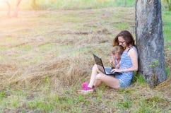 La madre y la hija jovenes están mirando el ordenador portátil al aire libre Fotos de archivo