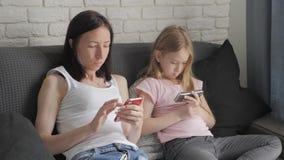 La madre y la hija jovenes est?n utilizando los artilugios que se sientan en el sof? en la sala de estar Familia moderna del conc almacen de metraje de vídeo