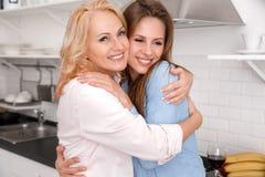 La madre y la hija juntas en casa weekend mirando la cámara alegre imagen de archivo