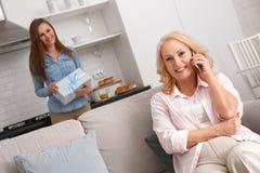 La madre y la hija juntas en casa weekend a la mujer que habla en el teléfono fotografía de archivo