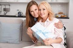 La madre y la hija juntas en casa weekend sosteniendo la caja de regalo imagenes de archivo