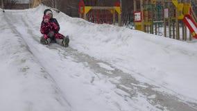 La madre y la hija juntas montan en una colina del hielo en un día de invierno, cámara lenta metrajes