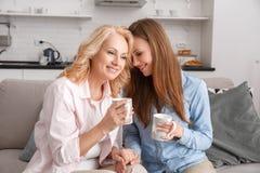 La madre y la hija junto en casa weekend el té caliente de consumición imagenes de archivo
