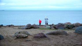 La madre y la hija lanzan piedras en el agua de la costa almacen de metraje de vídeo