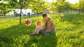 La madre y la hija pasan feliz el tiempo que juega juntas en la hierba en la puesta del sol almacen de video