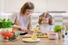 La madre y la hija que cocinan juntas en la ensalada, el padre y el ni?o vegetales de la cocina est?n hablando la sonrisa imágenes de archivo libres de regalías