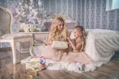 La madre y la hija salen un regalo de la Navidad de la caja Fotos de archivo