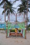 La madre y la hija se sientan en el banco con la cama agradable, el coco y la playa foto de archivo libre de regalías