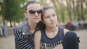 La madre y la hija se sientan en parque juntas y comparten un abrazo almacen de metraje de vídeo