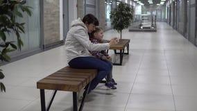 La madre y la hija toman selfies en un smartphone en una alameda o una oficina metrajes