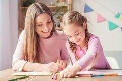 La madre y la hija weekend juntas en casa el dibujo con el primer de los lápices foto de archivo