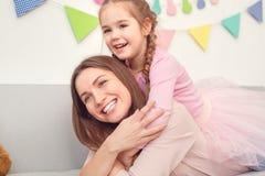 La madre y la hija weekend juntas en casa a la muchacha que se sienta en la parte posterior del ` s de la mamá imagenes de archivo