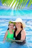 La madre y la hija abrazan en playa tropical de la piscina Imagen de archivo