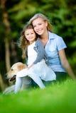 La madre y la hija con Labrador se sientan en la hierba imagenes de archivo