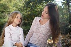 La madre y la hija de la conversación en el otoño parquean Imagen de archivo libre de regalías