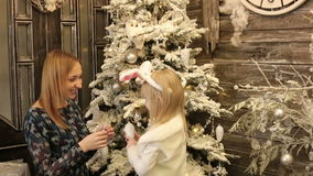 La madre y la hija en el traje blanco del conejo adornan el árbol de navidad almacen de metraje de vídeo