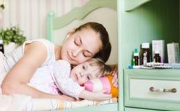 La madre y la hija enferma duermen juntas fotos de archivo libres de regalías