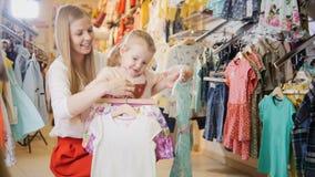 La madre y la hija están considerando en las manos de diversos equipos del bebé Imágenes de archivo libres de regalías