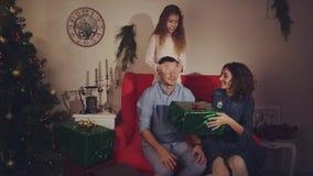 La madre y la hija felices de la familia dan un regalo de la Navidad al concepto del padre de regalo almacen de video