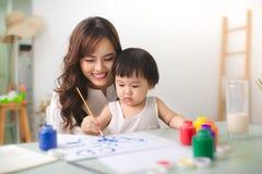 La madre y la hija felices de la familia juntas pintan Hel asiáticos de la mujer fotografía de archivo