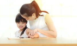 La madre y la hija felices de la familia leyeron un libro en casa Foto de archivo