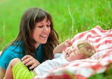 La madre y la hija felices tienen comida campestre al aire libre en hierba Imágenes de archivo libres de regalías