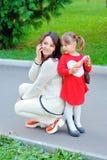 La madre y la hija hablan en el teléfono en el parque Foto de archivo libre de regalías