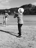 La madre y la hija juegan en la playa durante vacaciones de verano fotos de archivo