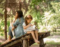 La madre y la hija leyeron un libro en el parque Imágenes de archivo libres de regalías