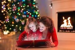 La madre y la hija leyeron un libro en la chimenea el Nochebuena Imagen de archivo
