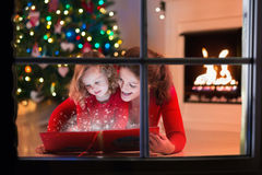 La madre y la hija leyeron un libro en la chimenea el Nochebuena Foto de archivo libre de regalías