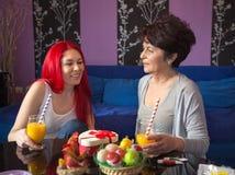 La madre y la hija mayores gozan en la consumición del zumo de naranja Imagen de archivo libre de regalías