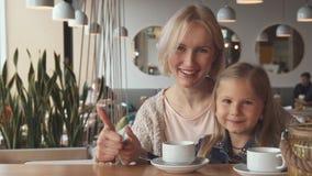 La madre y la hija muestra sus pulgares para arriba en el café almacen de video