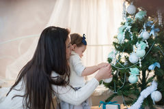 La madre y la hija que adornan un árbol de navidad juega, día de fiesta, regalo, decoración, Año Nuevo, la Navidad, forma de vida Foto de archivo