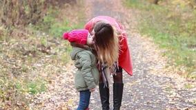 La madre y la hija que juegan el frotamiento sospecha en el bosque del otoño almacen de video