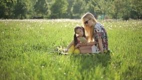 La madre y la hija que se sentaban en la hierba leyeron el libro en parque del verano en la puesta del sol almacen de metraje de vídeo