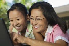La madre y la hija que se sientan en la tabla del patio trasero usando el ordenador portátil juntas se cierran para arriba Imagenes de archivo
