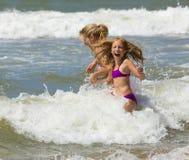 La madre y la hija rubias felices juegan entre ondas del mar Imagen de archivo
