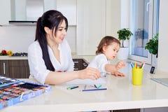 La madre y la hija se están divirtiendo mientras que dibuja en casa Fotografía de archivo libre de regalías