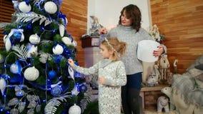 La madre y la hija se están preparando para el día de fiesta del Año Nuevo, familia que adorna un árbol de navidad, familia feliz almacen de metraje de vídeo