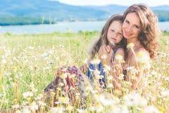 La madre y la hija se están sentando en campo de la manzanilla Foto de archivo libre de regalías