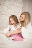 La madre y la hija se sientan en cama en pijamas y se divierten, utilizan el ordenador portátil lifestyle Familia feliz La educac Fotos de archivo libres de regalías