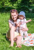 La madre y la hija se sientan en la hierba en el parque Fotos de archivo libres de regalías